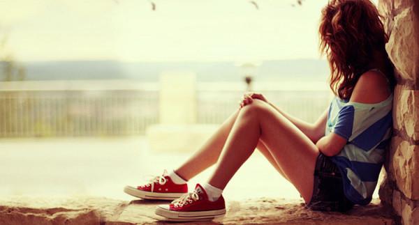 Smutna dziewczyna siedzi w oknie