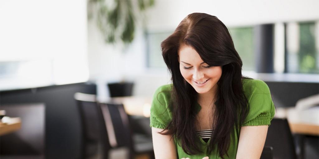 uśmiechnięta kobieta w ciemnych włosach w biurze