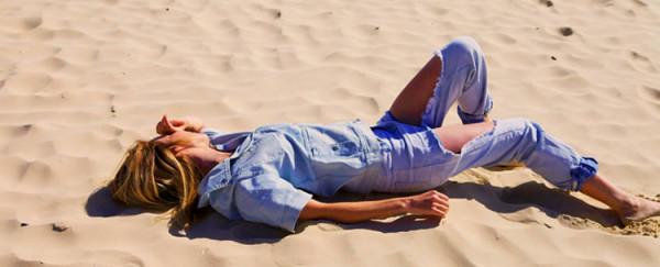 kobieta w spodniach jeans na plaży