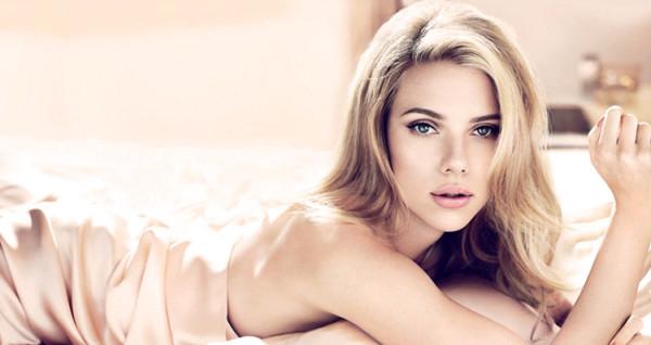 Scarlett Johansson leży na łózku z delikatnym makijażu i pięknych brawiach