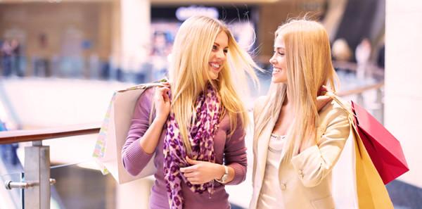 Dwie śliczne dziewczyny za zakupach w centrum handlowym uśmiechają się