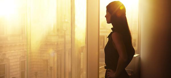 Piękna kobieta w biznesie jest w pracy i opserwuje miasto o zachodzie słońca