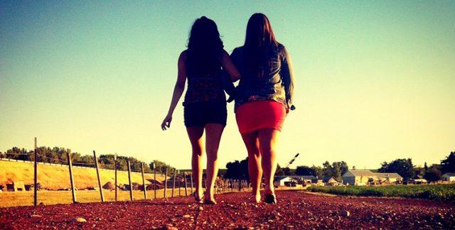 dwie dziewczyny idąza rękę w słoneczny dzień