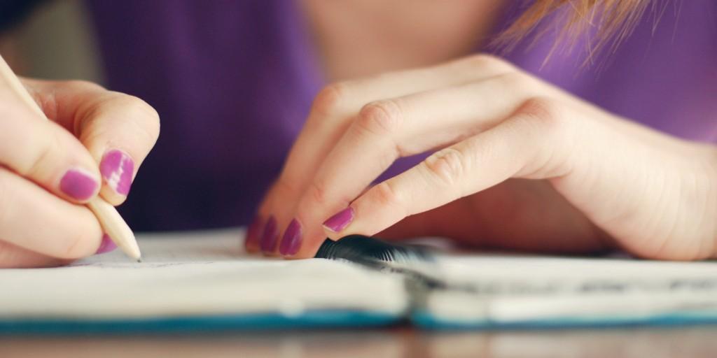 kobieta pisząca w zeszycie na biurku