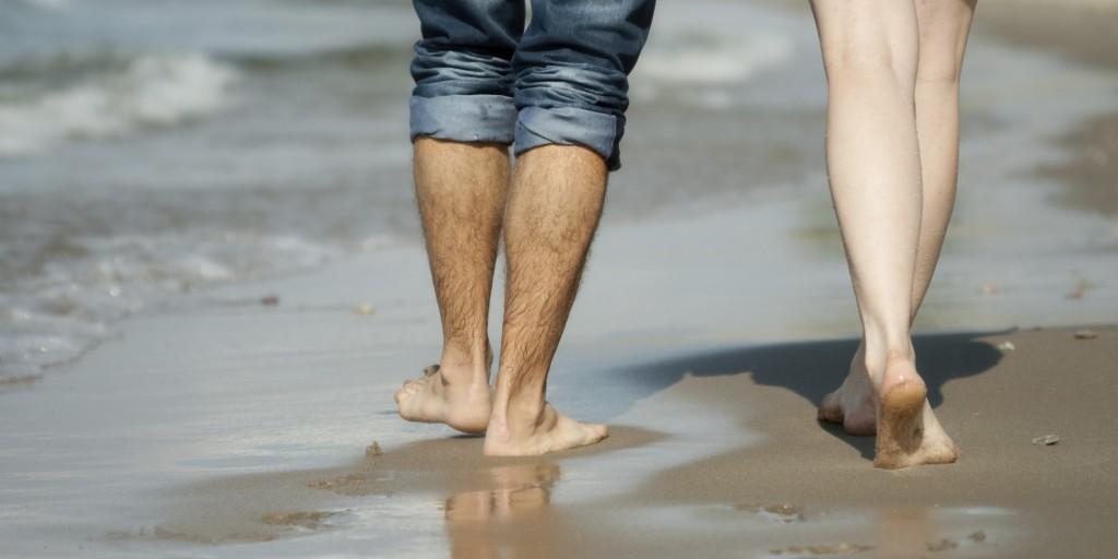para kobieta i mężczyzna spacerują razem na boso wzdłóż morza