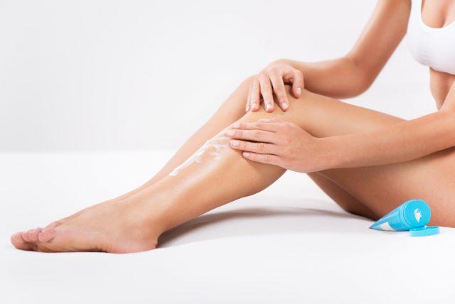 piękna kobieta smaruje kremem nogi