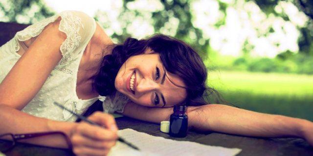 kobieta pisze i leży na trawie