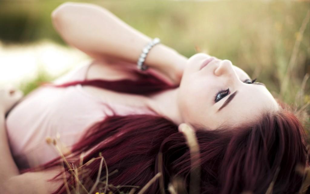 smutna dziewczyna leży na trawie