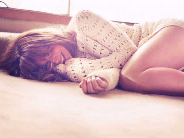 piękna kobieta w swetrze leży na kanapie